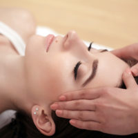 Spa relaxation, skincare, healthy pleasure concept. Woman lying with closed eyes having relaxing face massage